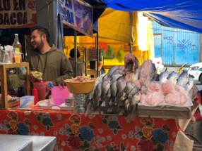 Man sells fish at a stall in an outdoor market